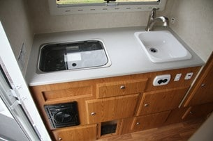 Köket har stor arbetsyta. Notera värmefläkten nedanför spisen samt 12-voltsuttag och USB-port.