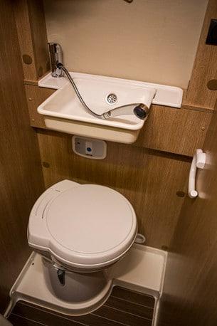 Kranen i vasken dubblerar som duschmunstycke. Handfatet går att fälla upp mot väggen.