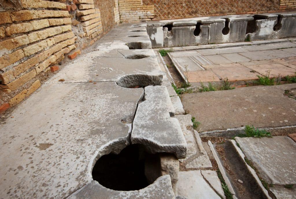 En antik toalett i Ostia Antica, Italien. Romarna ansåg sig inte behöva avskildhet vid toabesöket.